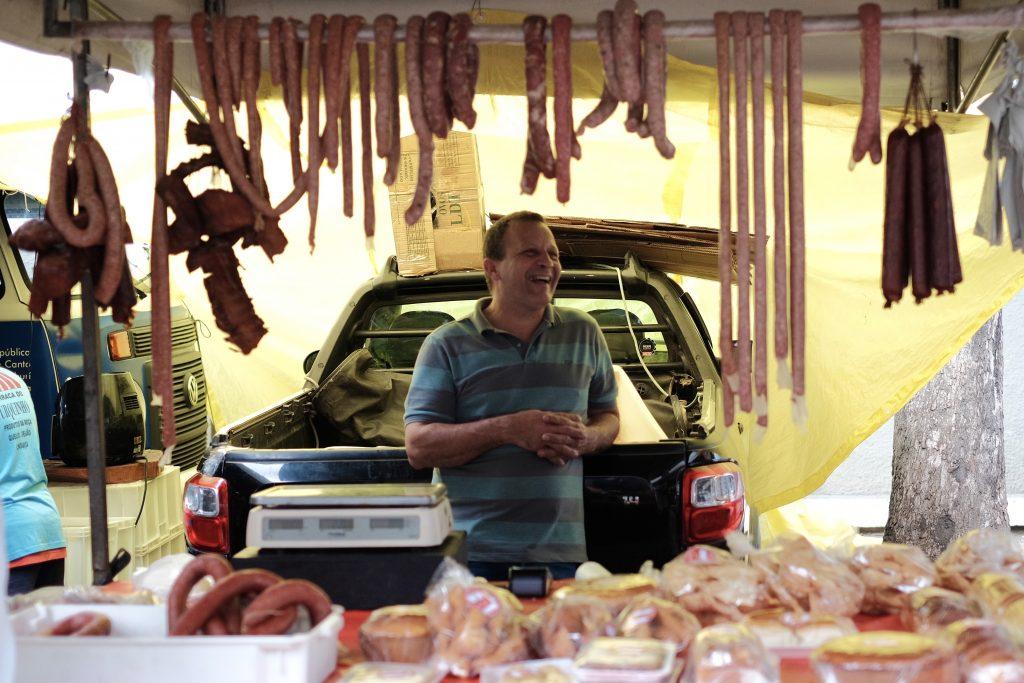 Foto de um vendedor de linguiças, tirada no exato momento em que ele sorri para algum terceiro.
