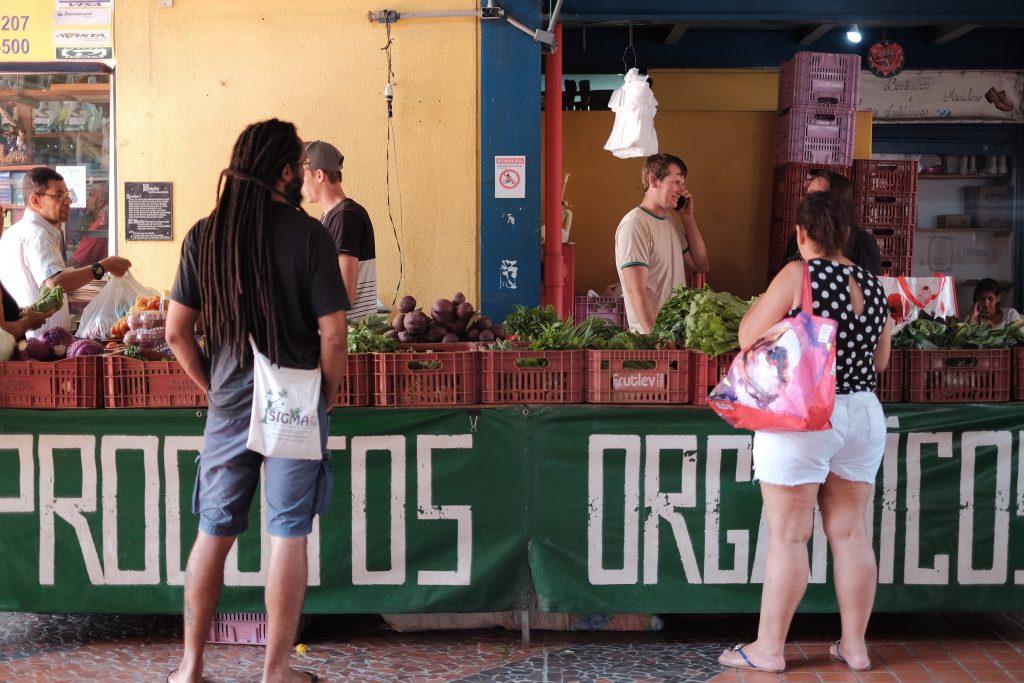 """Foto de uma bancada de hortaliças com um grande letreiro """"Produtos Orgânicos"""". É uma foto sem nada de especial."""